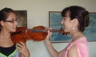 Jennifer showing a student where to place a violin on the left shoulder